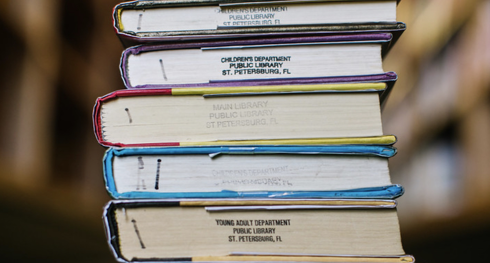 """A stack of library books with """"Public Library St. Petersburg Florida"""" printed on the sides."""