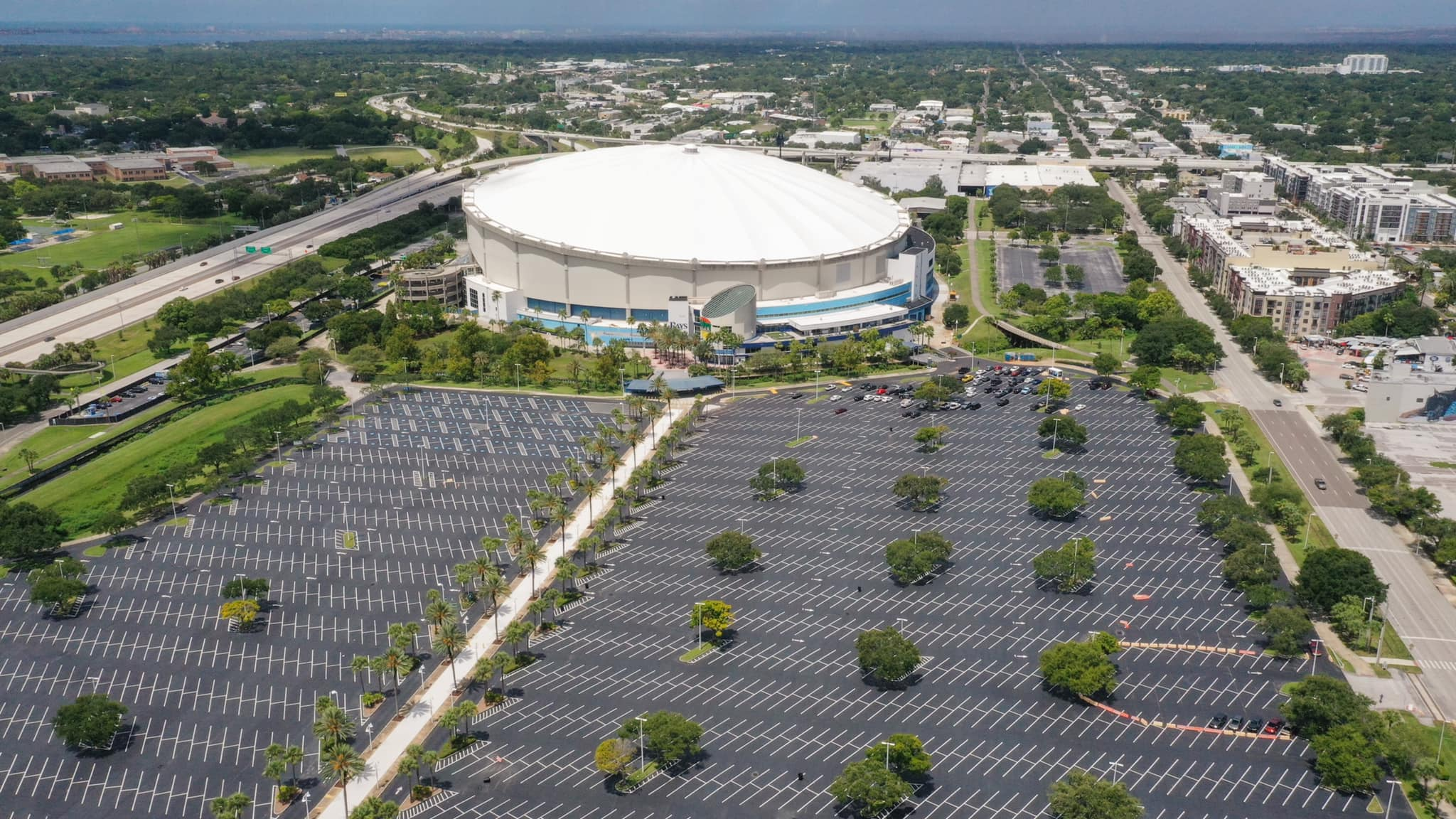 An aerial photo of Tropicana Field in St. Petersburg Florida with a view of the parking lot and dome.