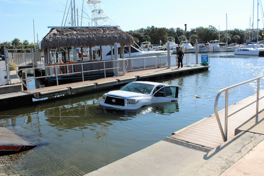 A white Toyota truck almost completely submerged at a marina boat dock.