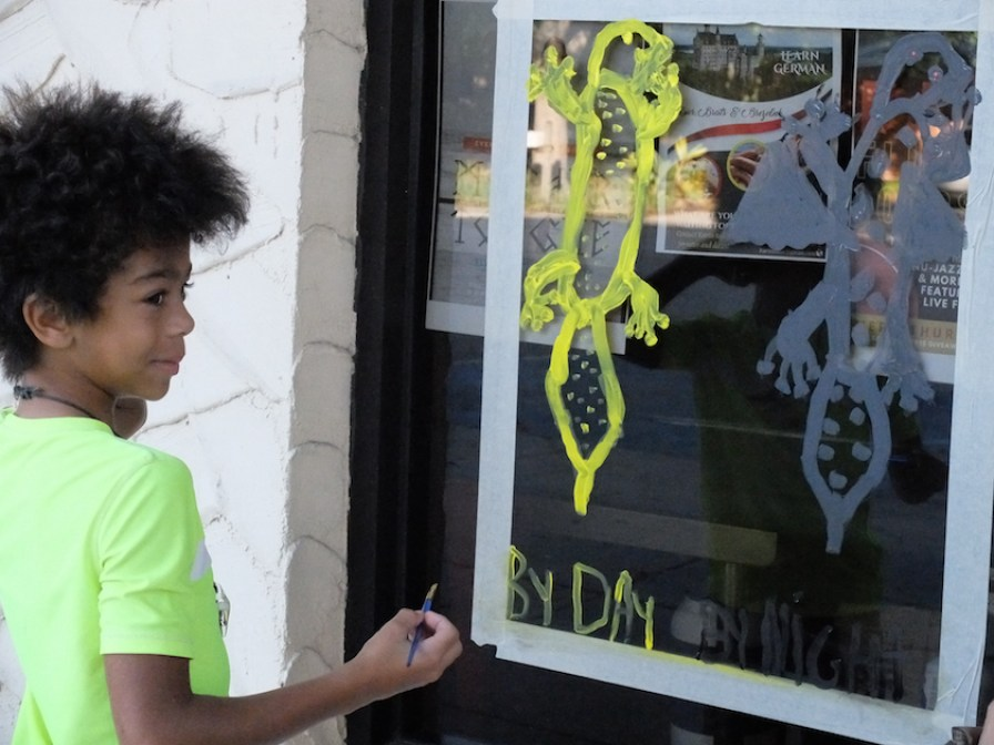 A little boy in a lime green shirt painting a colorful scene on a shop window.