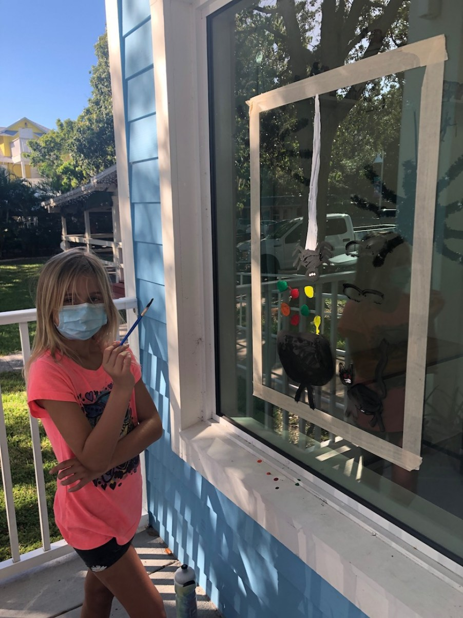 A girl in a neon orange top and a blue face mask stands in front of a window painting while holding a paint brush and looking at the camera.