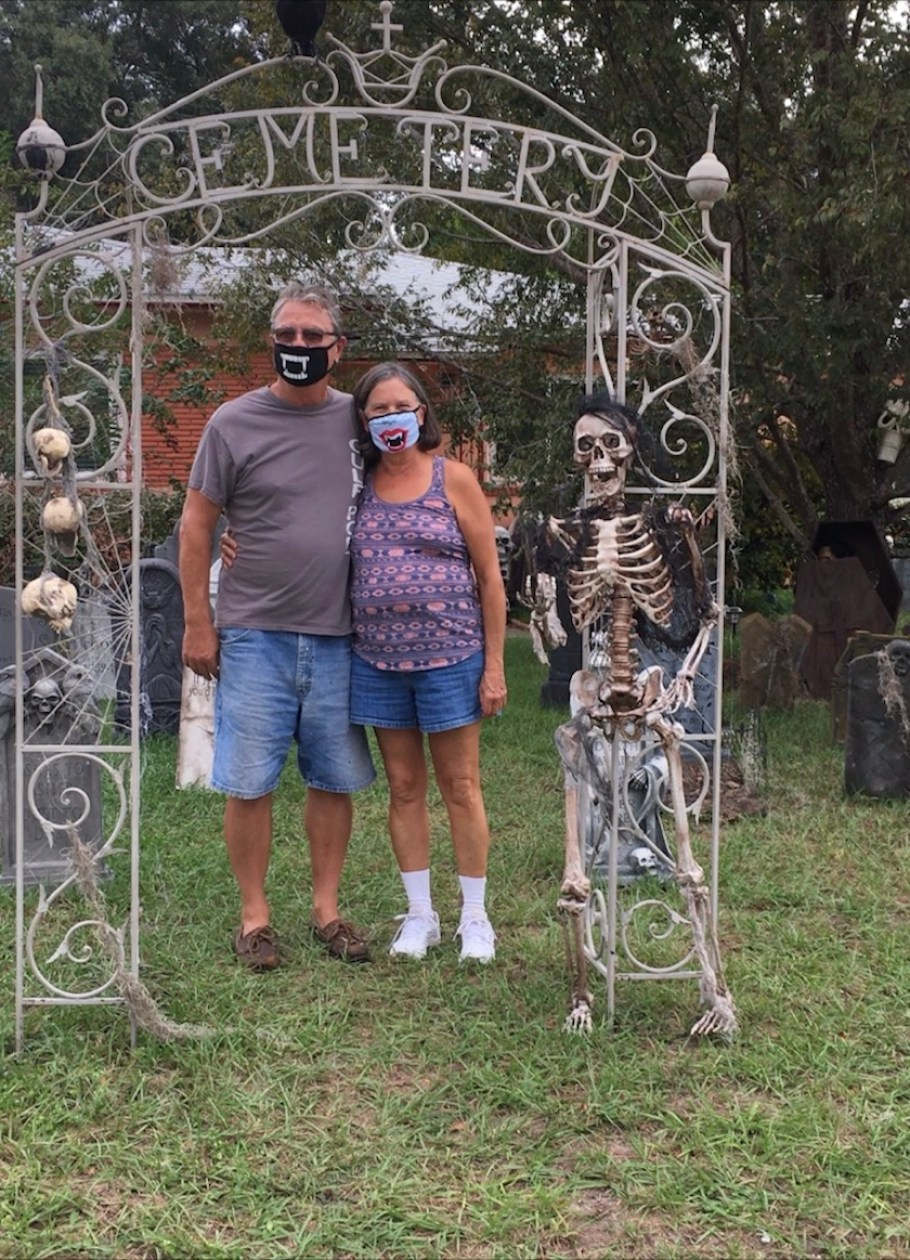 """A mand and a woman in face masks stand together under a metal gate that reads """"Cemetery."""""""