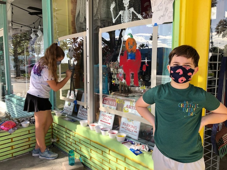 A little boy in a green top and face mask stands in front of a window he has painted with a halloween design. A girl is painting a window behind him.
