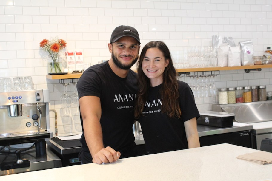 A man and woman stand together at a restaurant counter wearing black t-shirts and smiling at the camera.