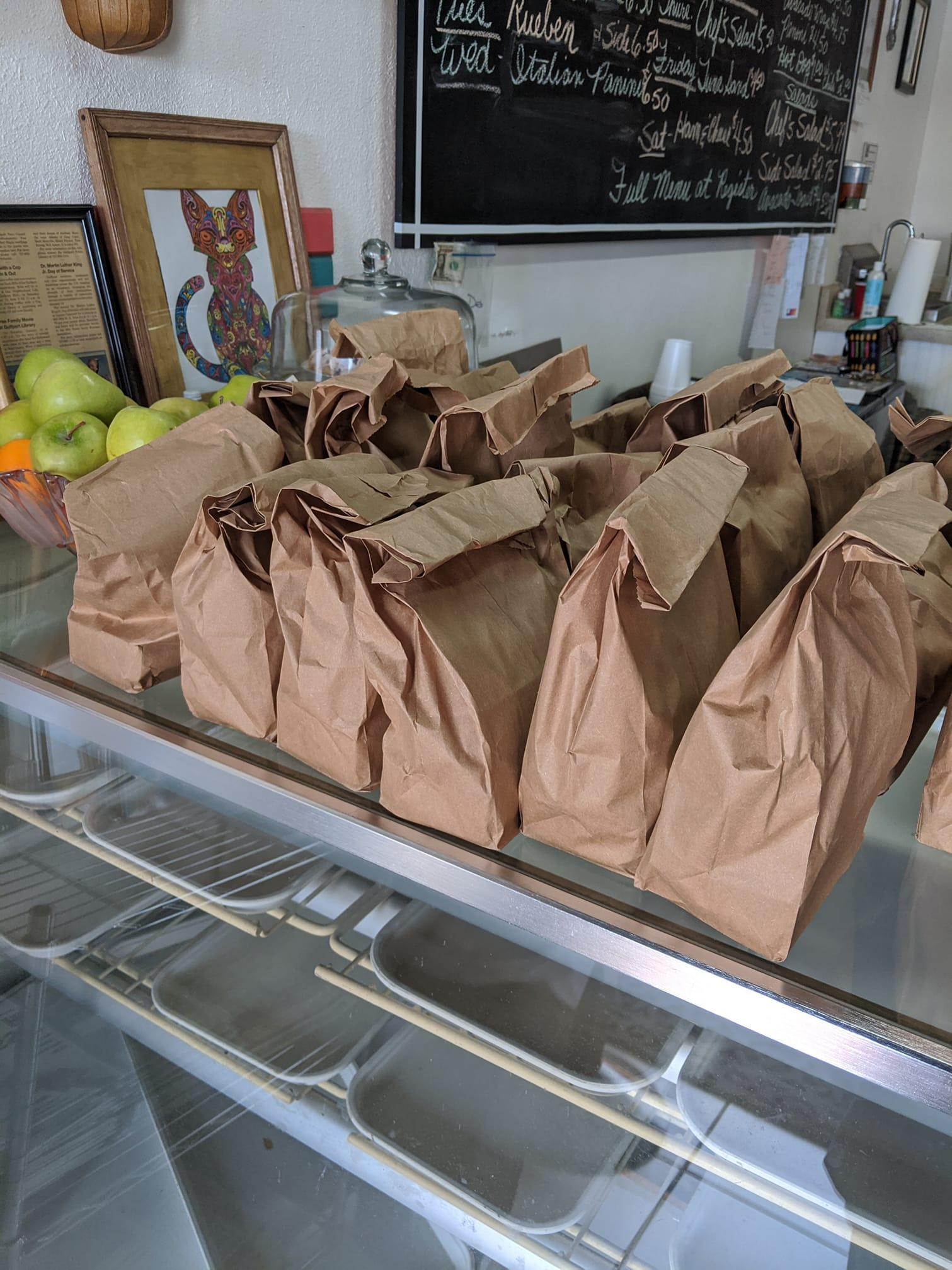 A group of lunches in brown paper bags.