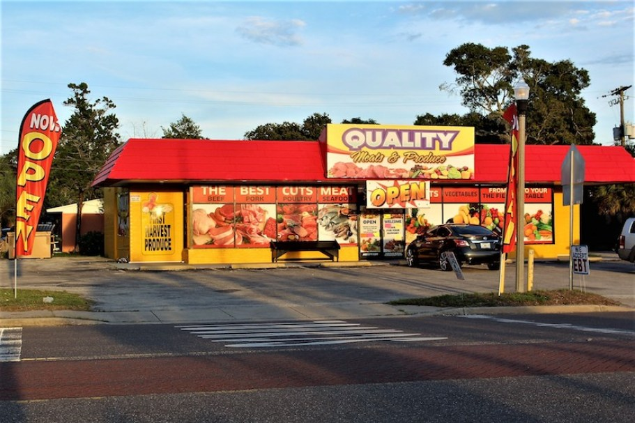 "The outside shot of a store with a sign that reads "" Quality Meats and Produce"""