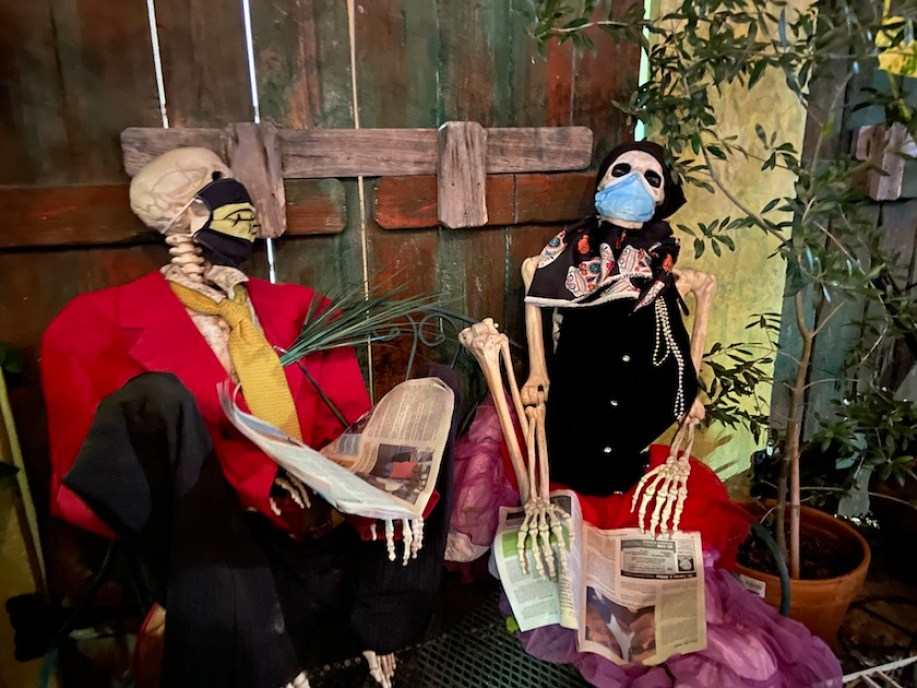 Fake skeletons dressed in clothes reading newspapers