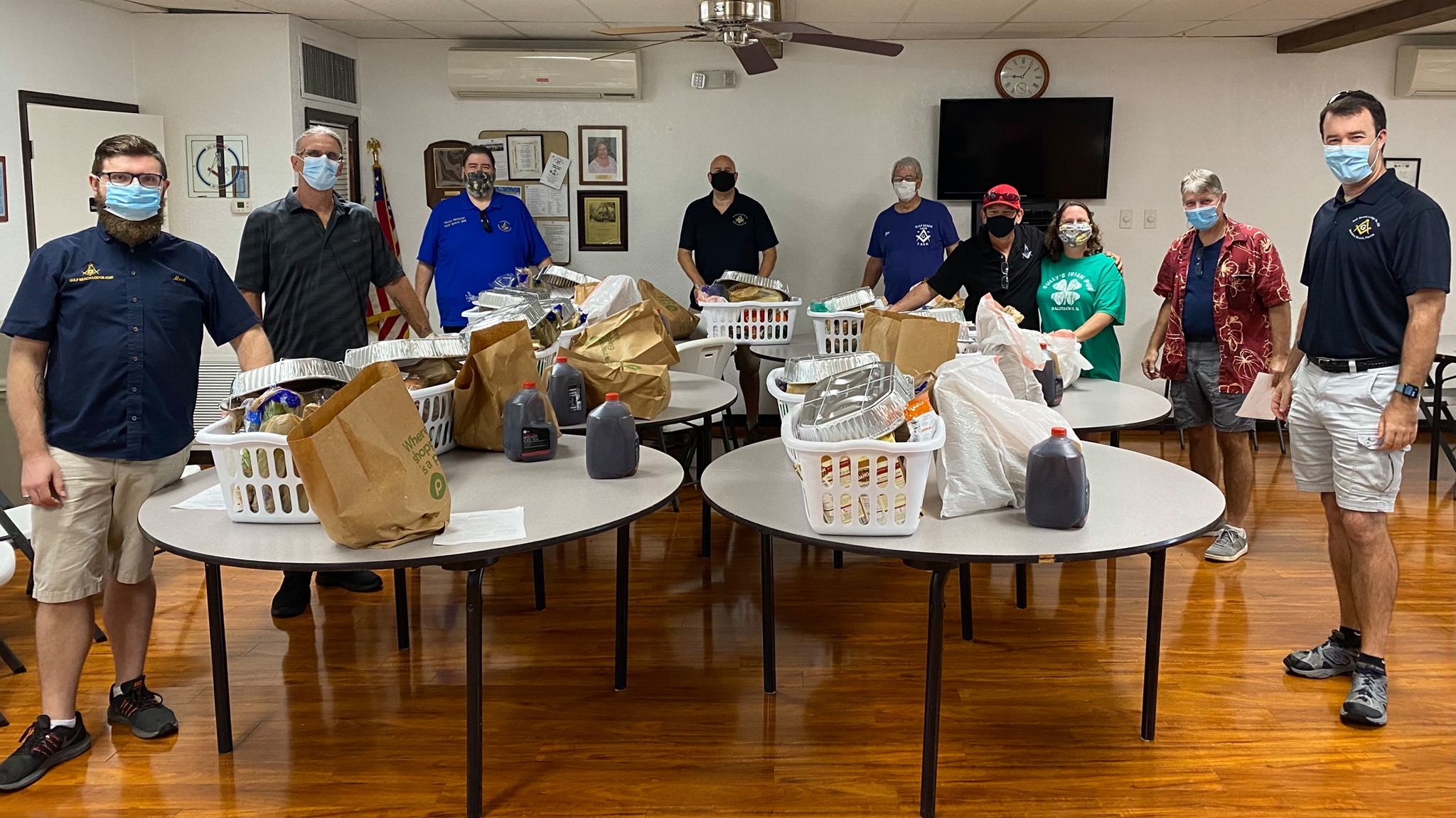 A group of people in a room with face masks on and baskets of Thanksgiving food supplies.