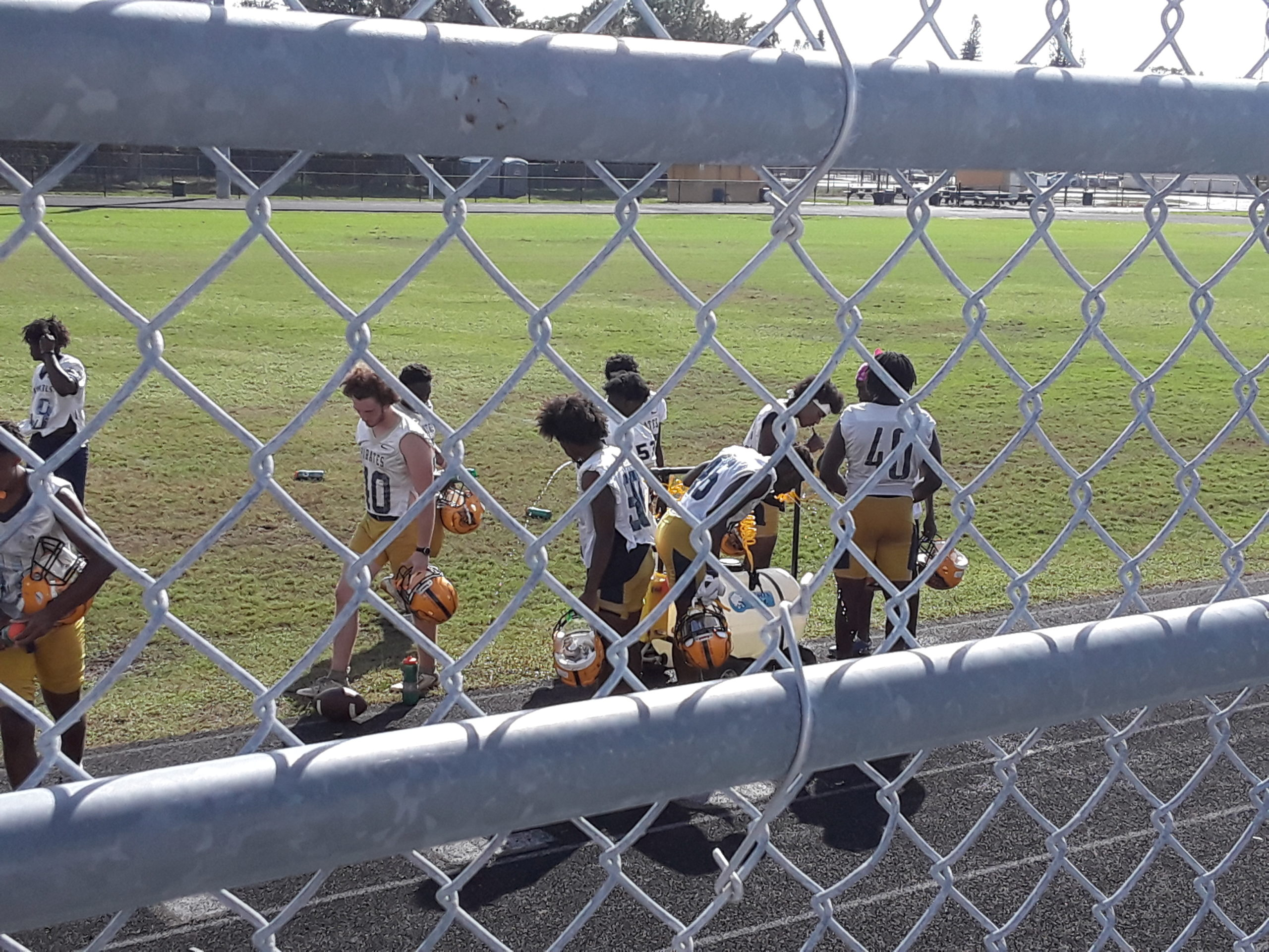 A football team practice photographed through a chainlink fence.