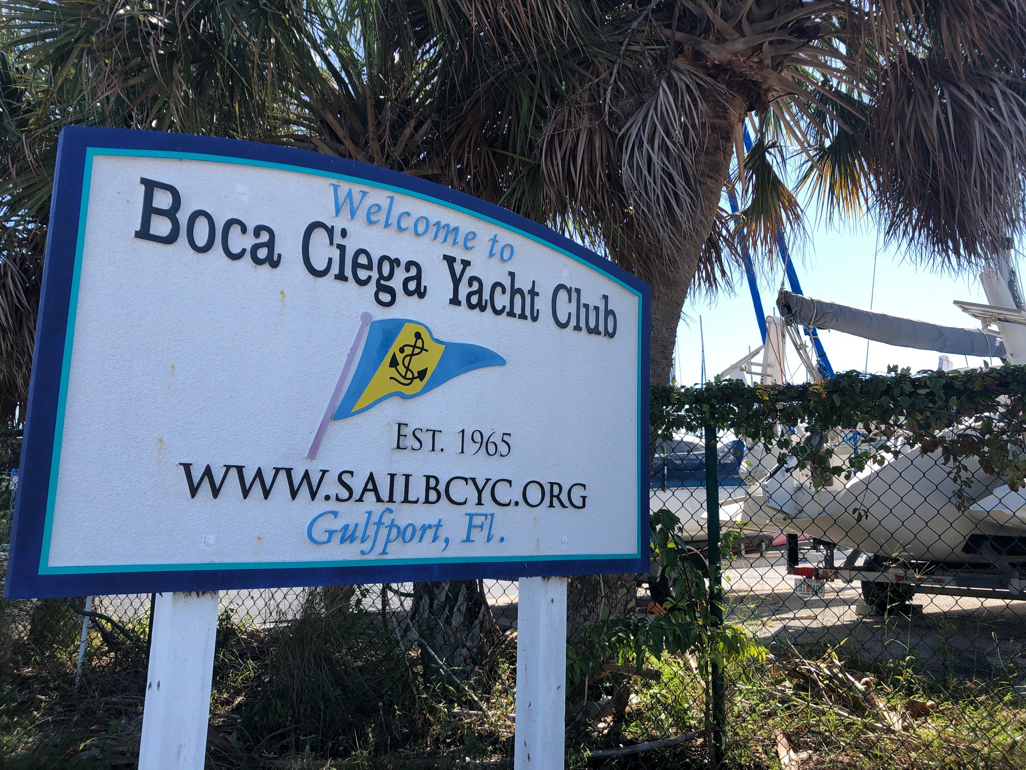 """A whit sign with blue lettering that reads """"Welcome to Boca Ciega Yacht Club, Set. 1965, www.sailbcyc.org, Gulfport, FL"""""""