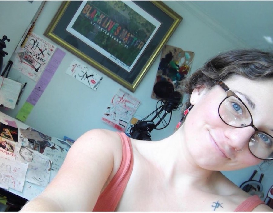 An angled selfie of a girl in a tank top with a framed picture in background.