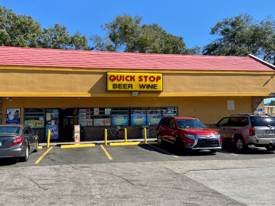 """The outside of a convenience store with cars parked in front; the sign reads """"Quick Stop, Beer Wine"""""""