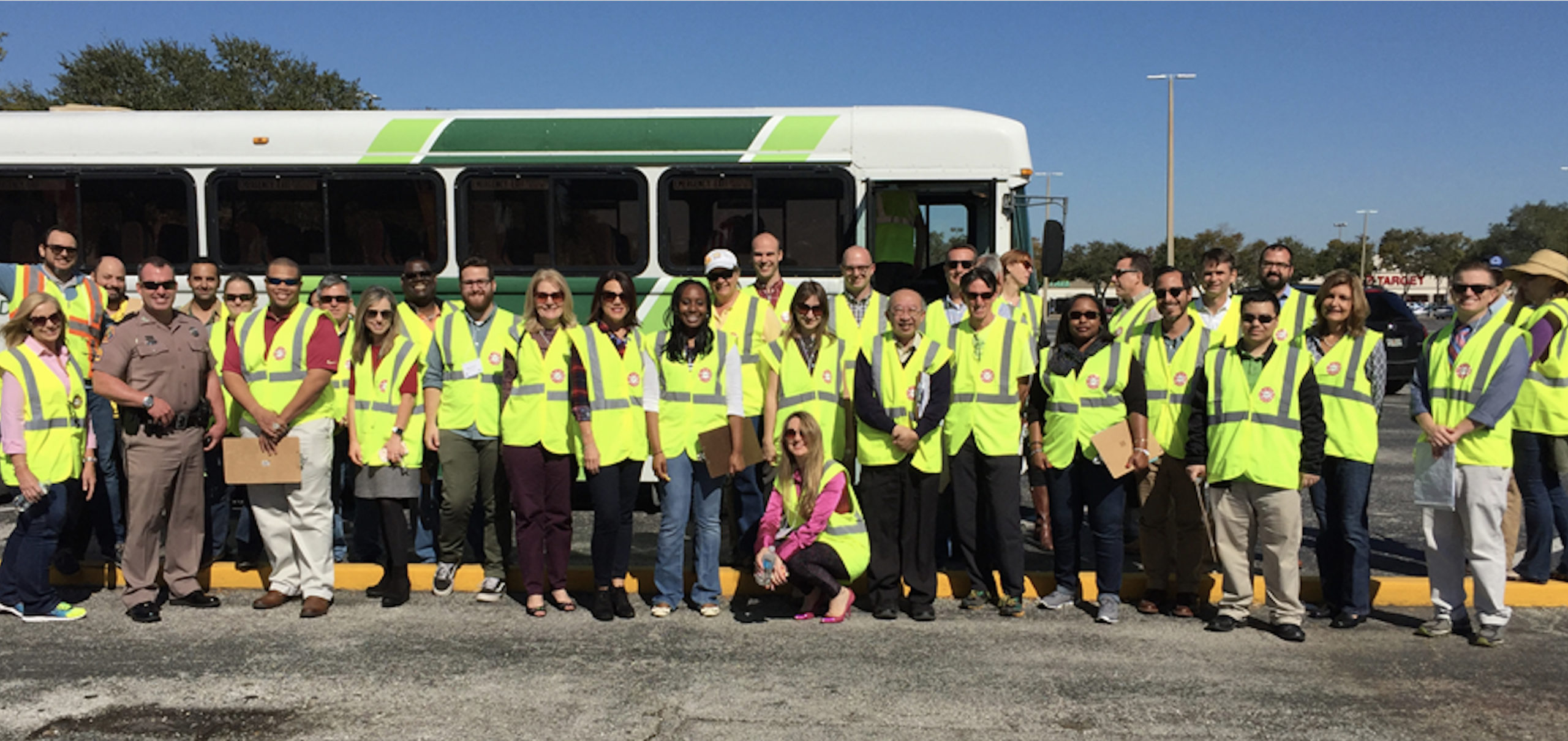 A group of people in safety vests standing outside in front of a bus