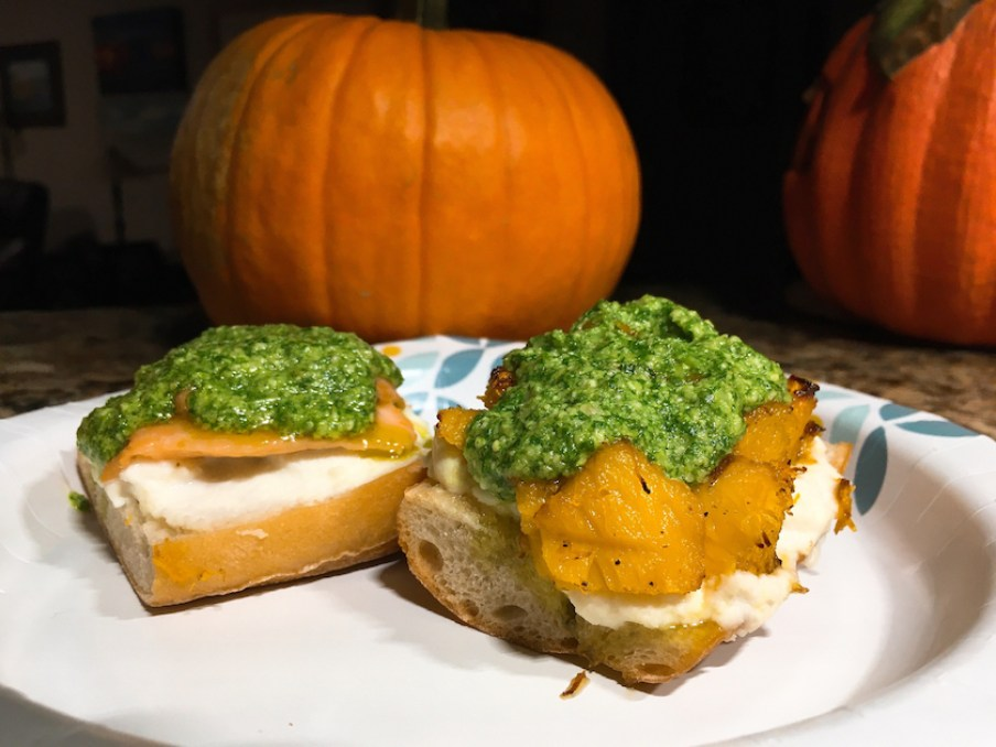 Pumpkin bruschetta with green sauce and a pumpkin in the background.