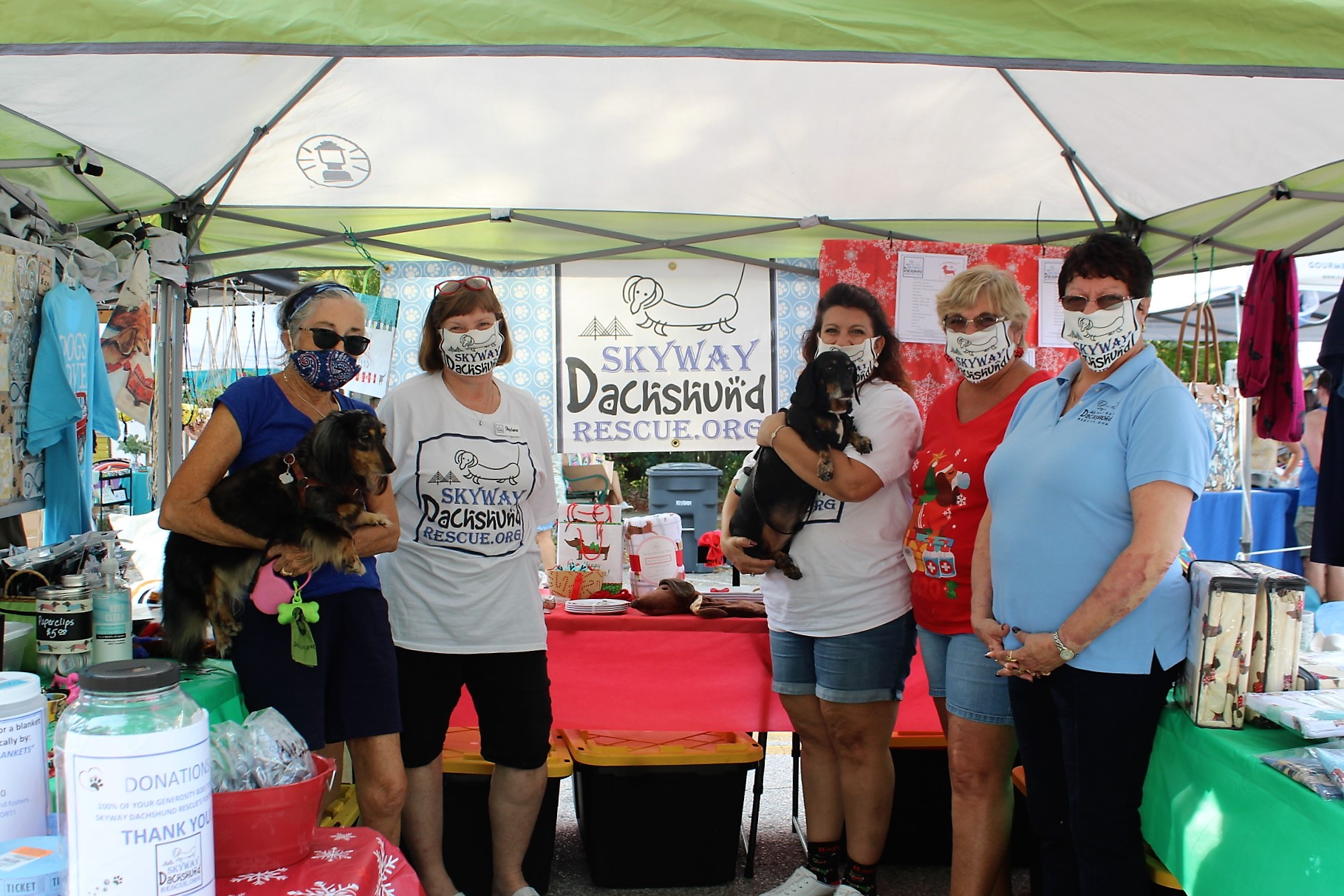 A group of people in a tent wearing face masks with a dachshund