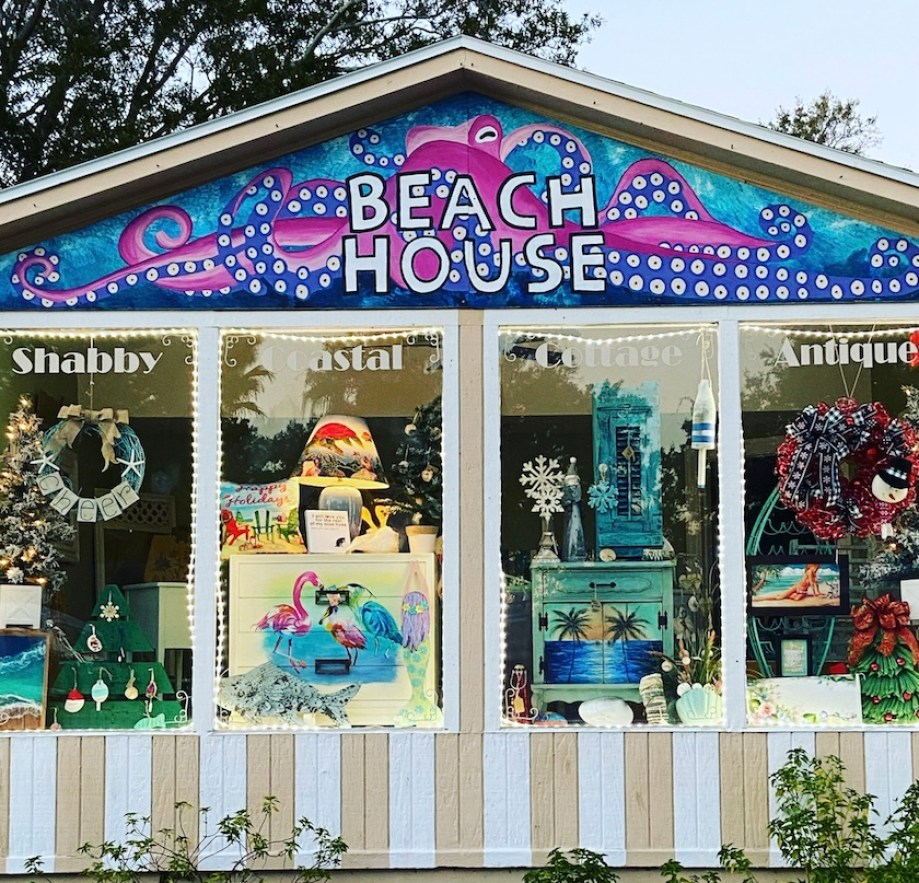 "Outside of an art gallery with a multicolored sign that reads ""Beach House"""