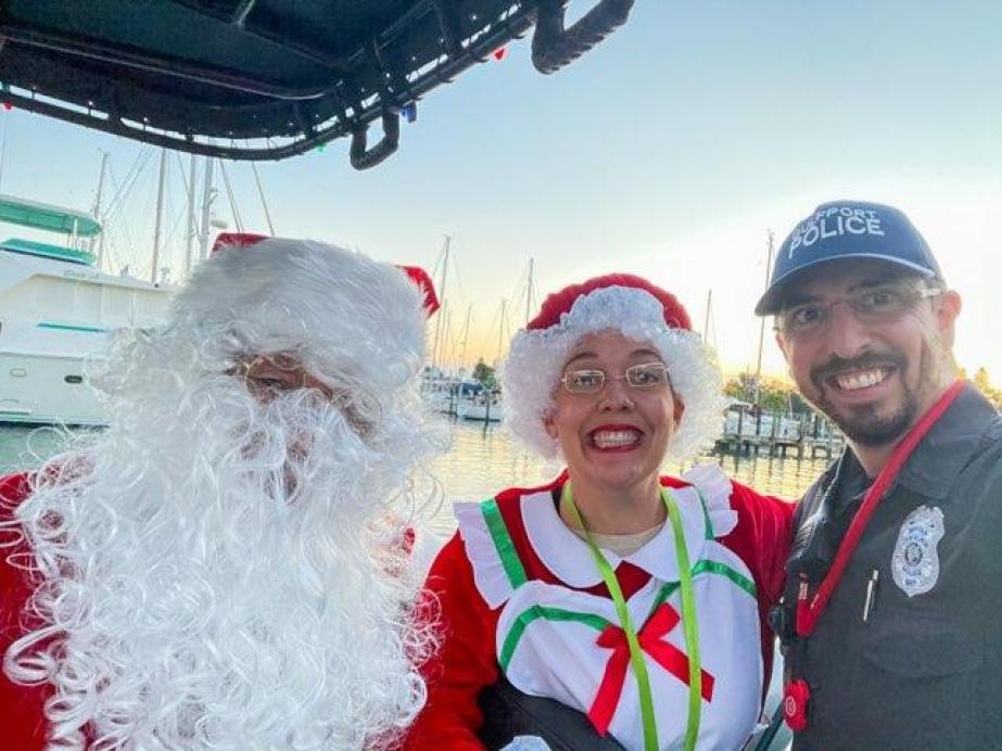 A man and woman dresses as Santa and Mrs. Claus, and another man, on a boat in a marina at sunset.