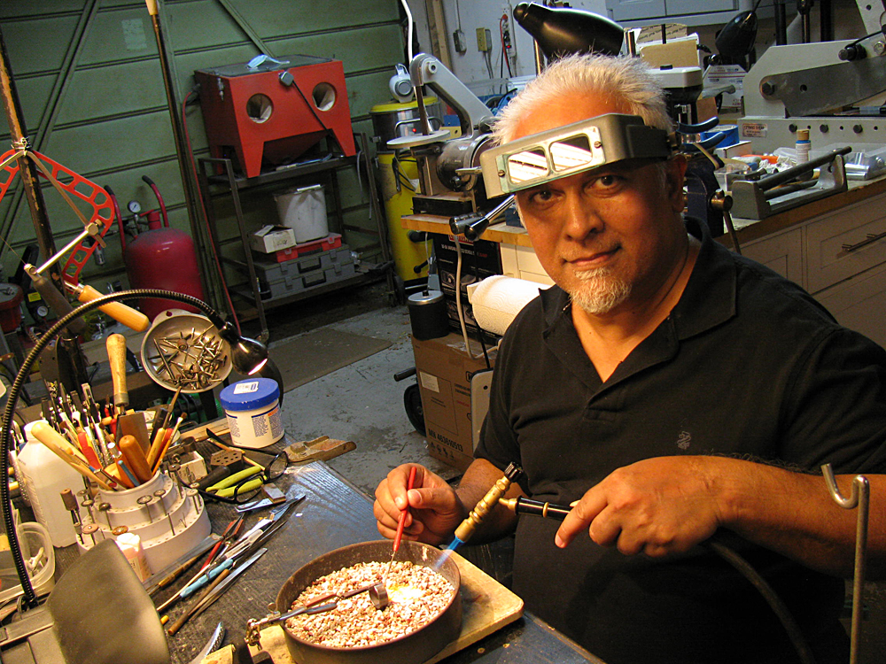 A man working on jewelry making with magnifiers on his head.