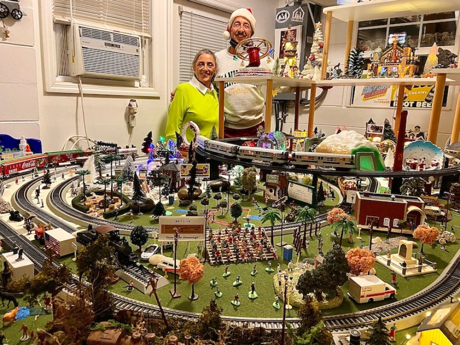 A massive model train setup with a holiday these; a man and a woman stand behind it.