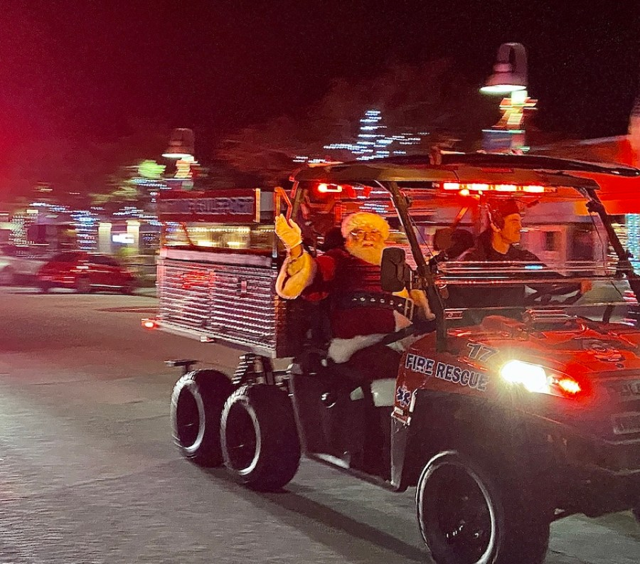 A man dressed as Santa in an ATV waving