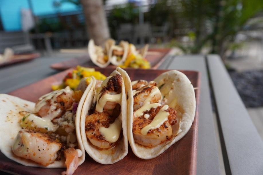 A close up photo of shrimp tacos outdoors.