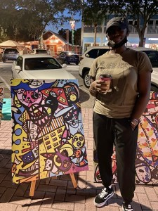 A woman in a hat, t-shirt and black pants stands next to a piece of colorful abstract art outside