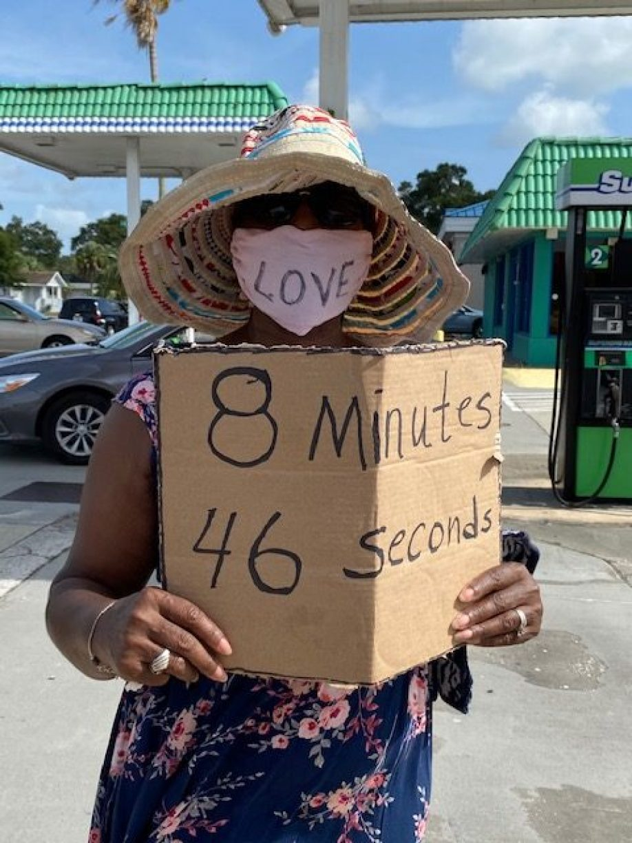 "A woman in a hat, sunglasses and blue face mask holding a cardboard sign that reads ""8 Minutes 46 seconds"""