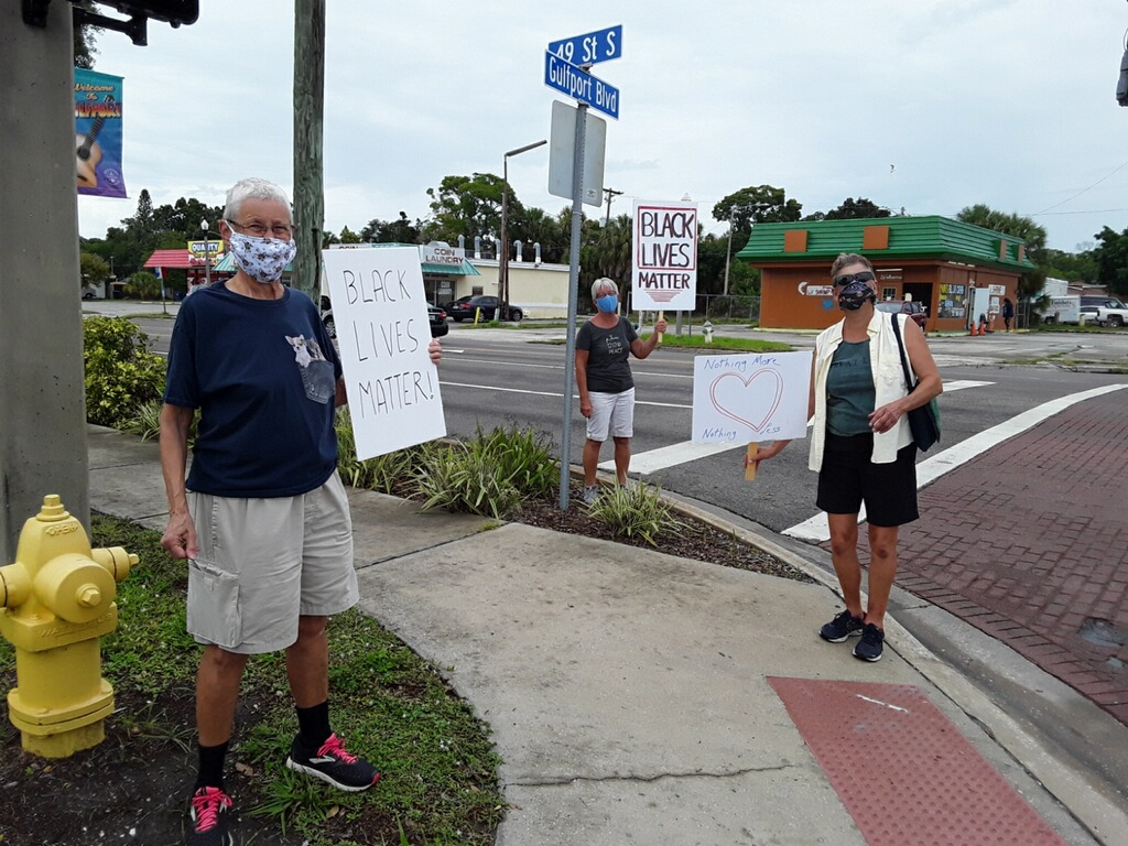 Three people standing on a corner holding signs that read Black Lives Matter""