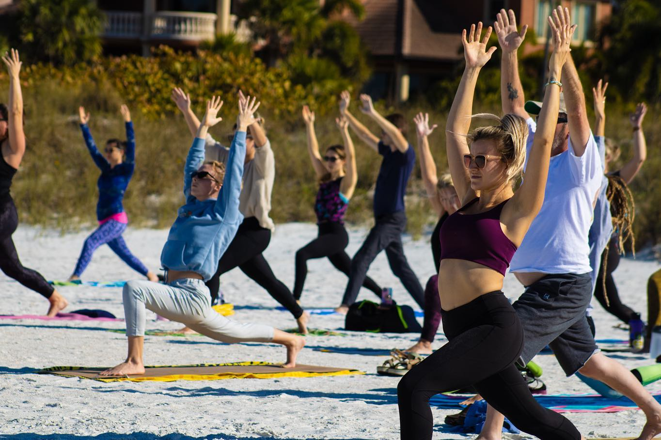 Men and women standing up and striking a yoga pose on the beach in community yoga