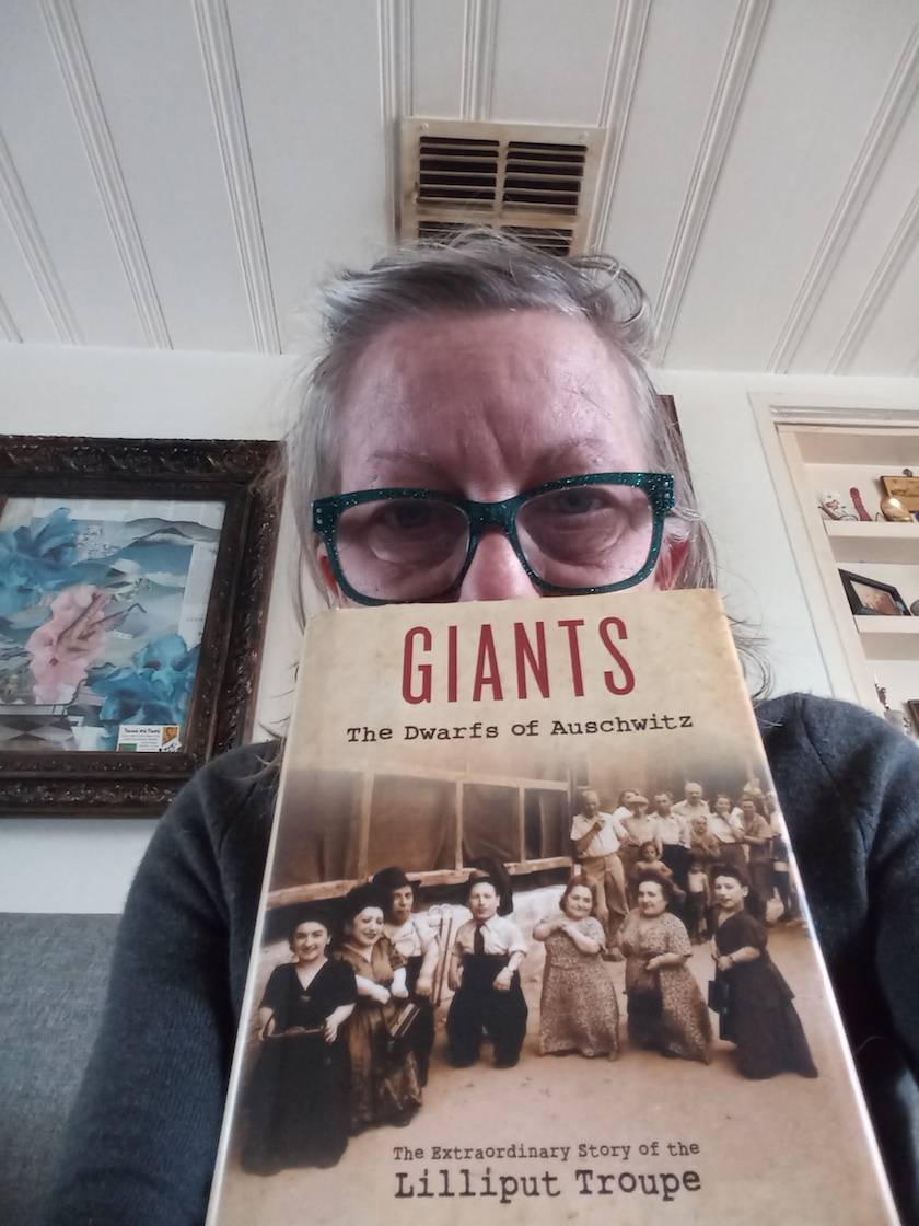 """A woman with glasses holding a book that says """"Giants"""""""