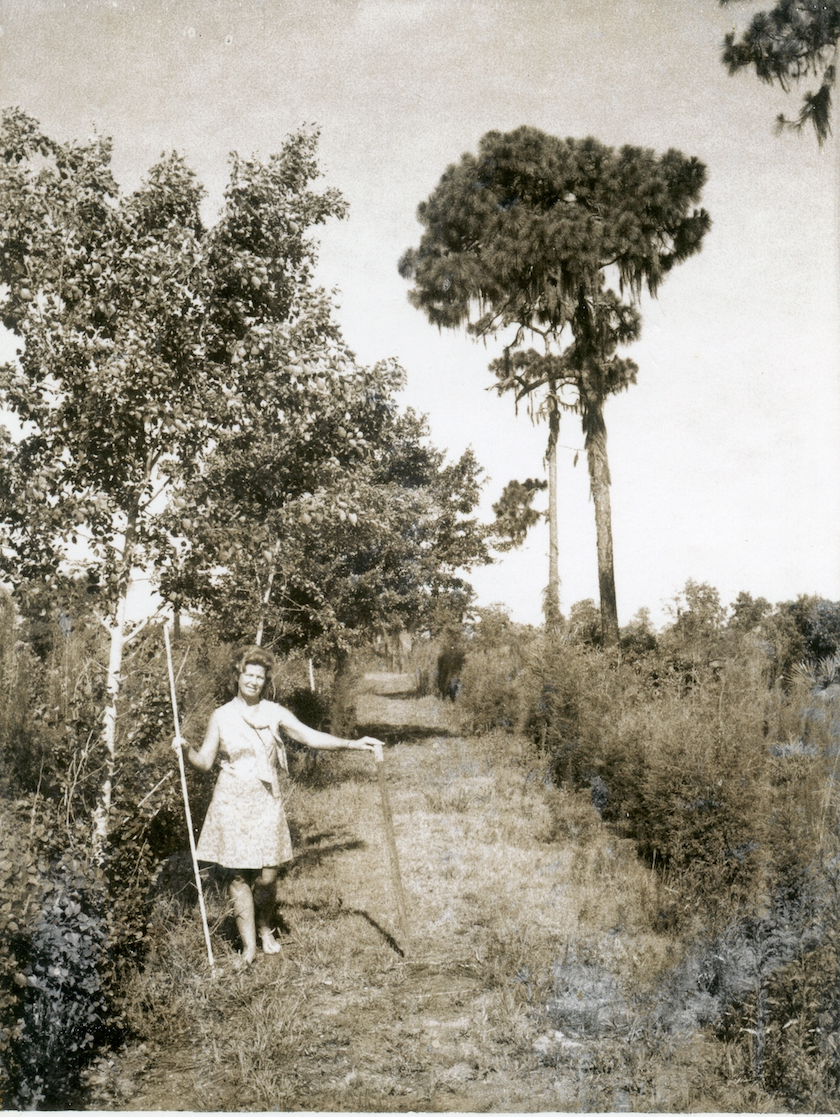 A vintage sepia photo of a woman in a nature setting, standing in a dirt road