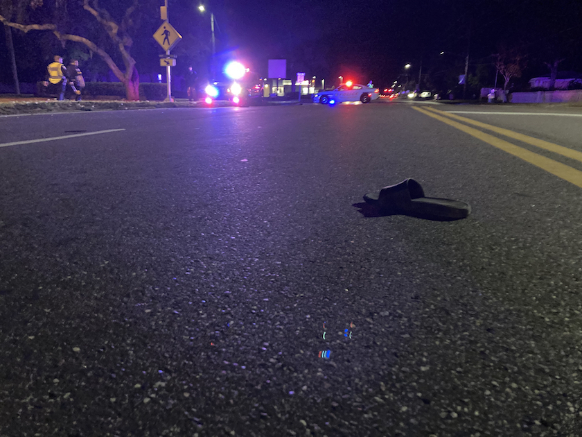 A night crash scene with blue and red police lights.