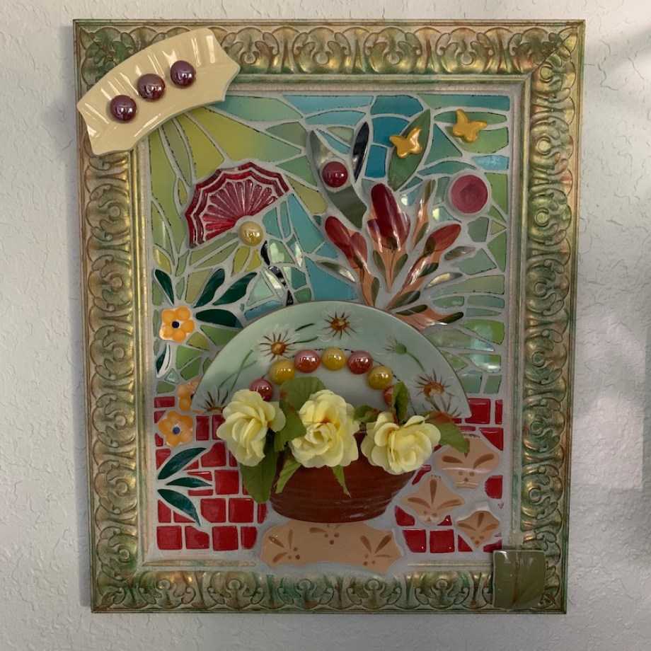 A mosaic tile art in a rectangular frame depicting flowers