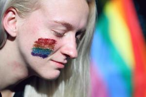 Blonde woman white a glitter rainbow painted on her face in front of a gay flag.