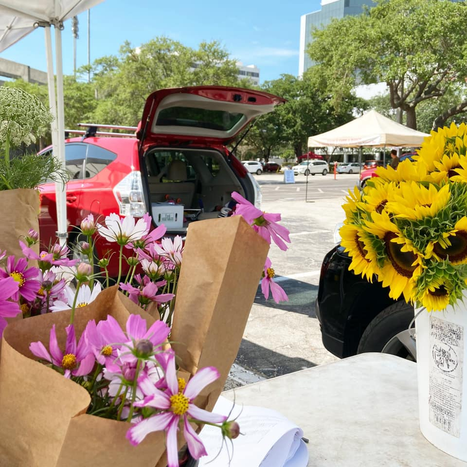 Bouquets of flowers framing a distanced open-trunked SUV