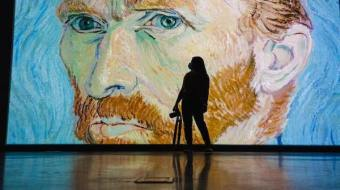 A blue-hued Van Gogh painting, large scale, with the silhouette of a woman.