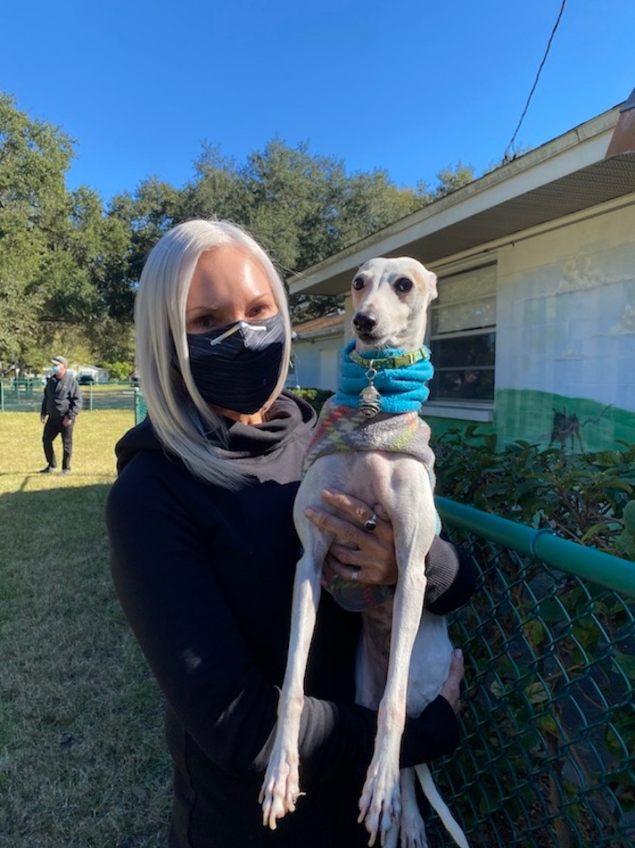 A woman in a face mask holds an Italian greyhound in a sweater outside