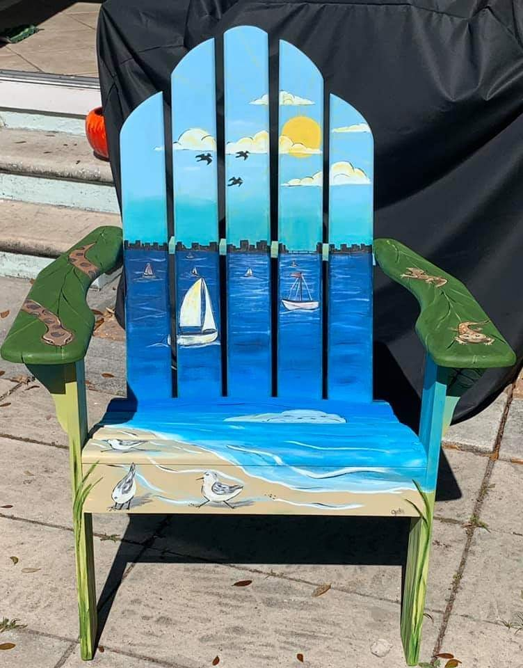 Blue wooden lawn chair with a beach background painted on
