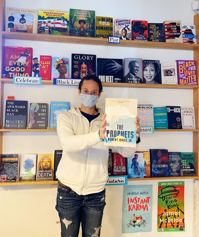 """A woman in a face mask in front of a wall of books holding up a book titled """"The Prophets"""""""