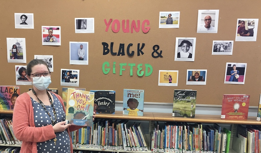 """A woman holding up a book in front of a library display that reads """"Young, Black & Gifted."""""""