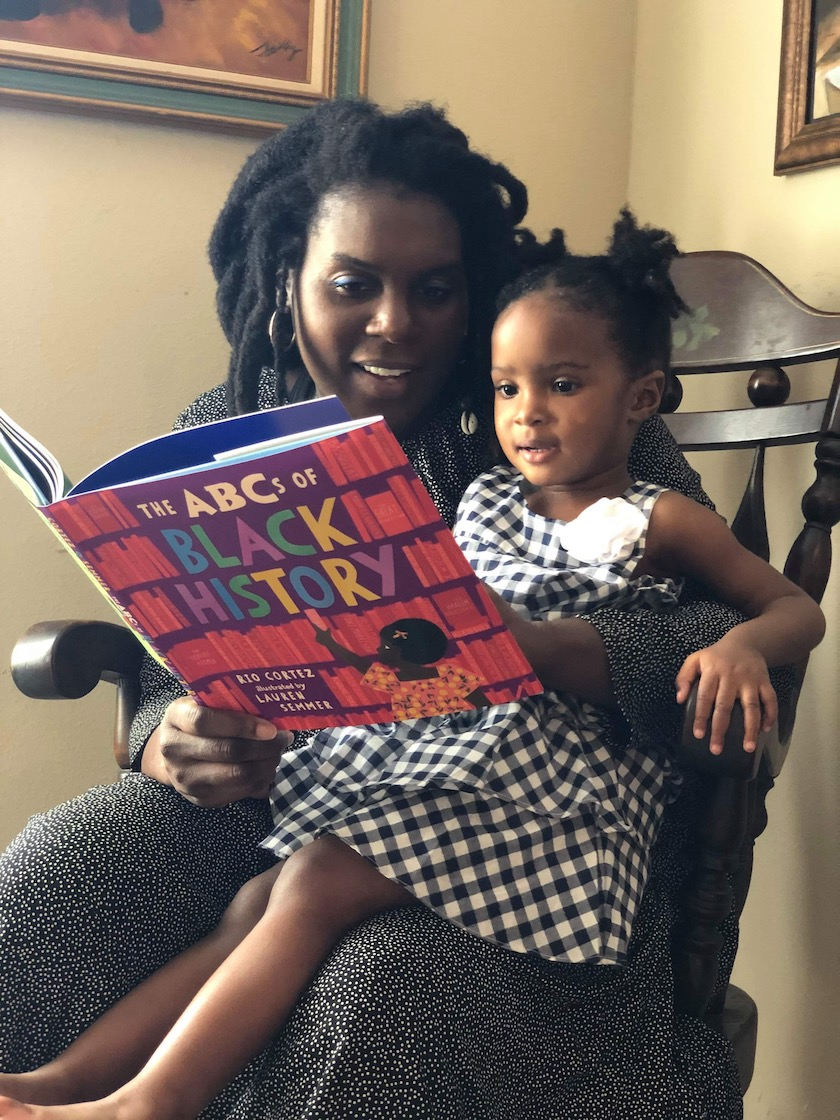"""A woman reading a book called """"The ABCs of Black History"""" to a young girl in a rocking chair"""