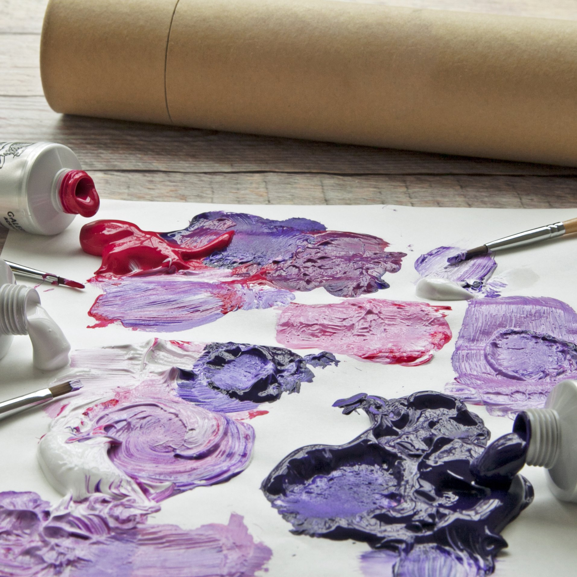 Purple and pink paints smeared across a white canvas with open paint containers laid out.