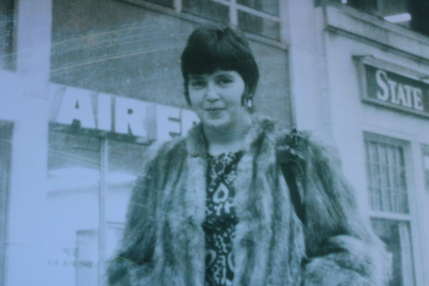 An older photo of a lady in a fur coat with short dark hair