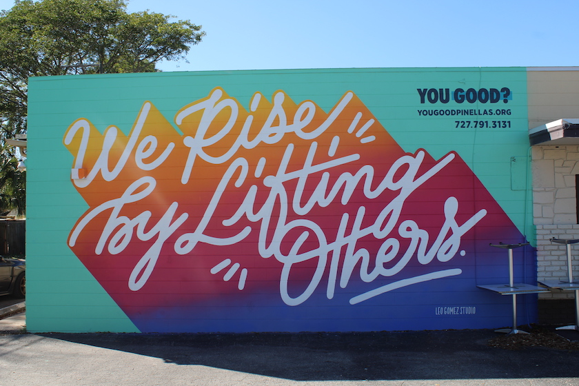 "A colorful mural that reads ""We Rise By Lifting Others"""