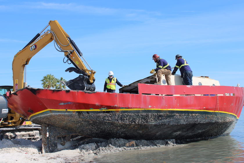 Workers dismantle a large red boat on a beach.