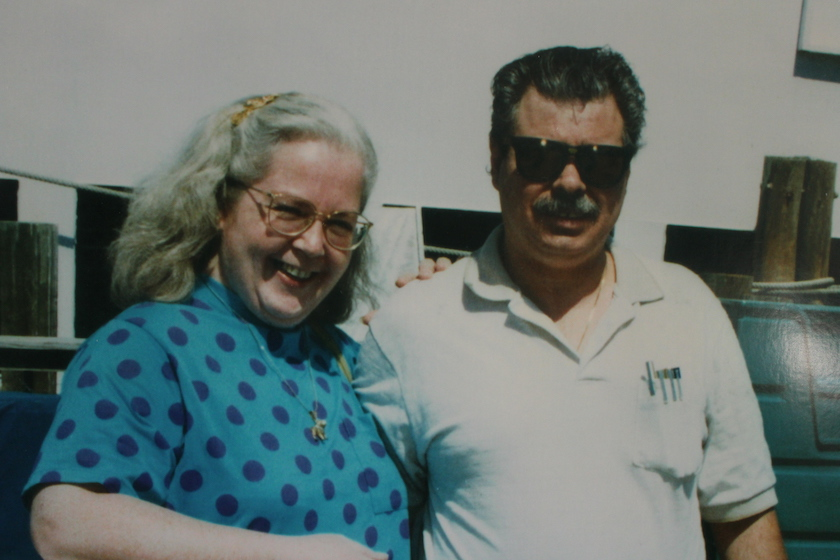 An older photo of a man in sunglasses with a lady in a blue polka dot shirt