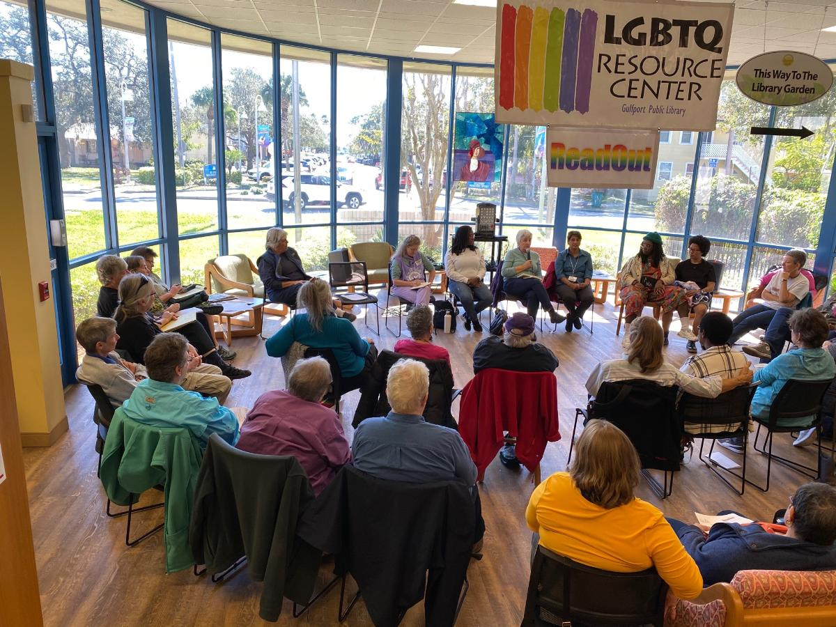 """A group of people sitting in a library with an """"LGBTQ"""" sign above them."""