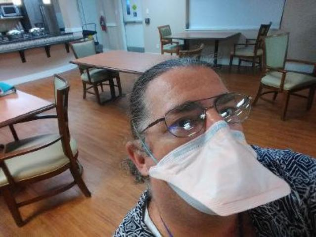 A selfie photo of a man in glasses and a white facemark standing in an empty cafeteria
