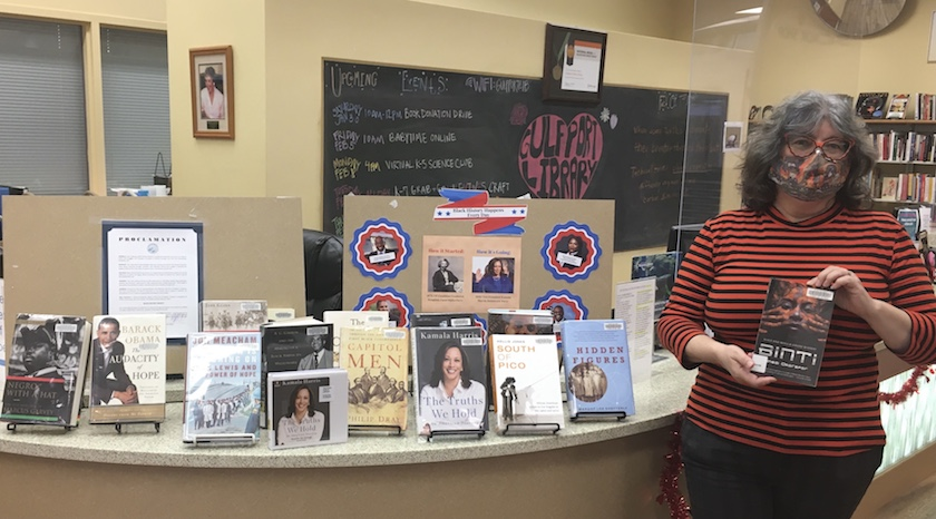 A woman holding up a book in front of a library book display for Black History Month.