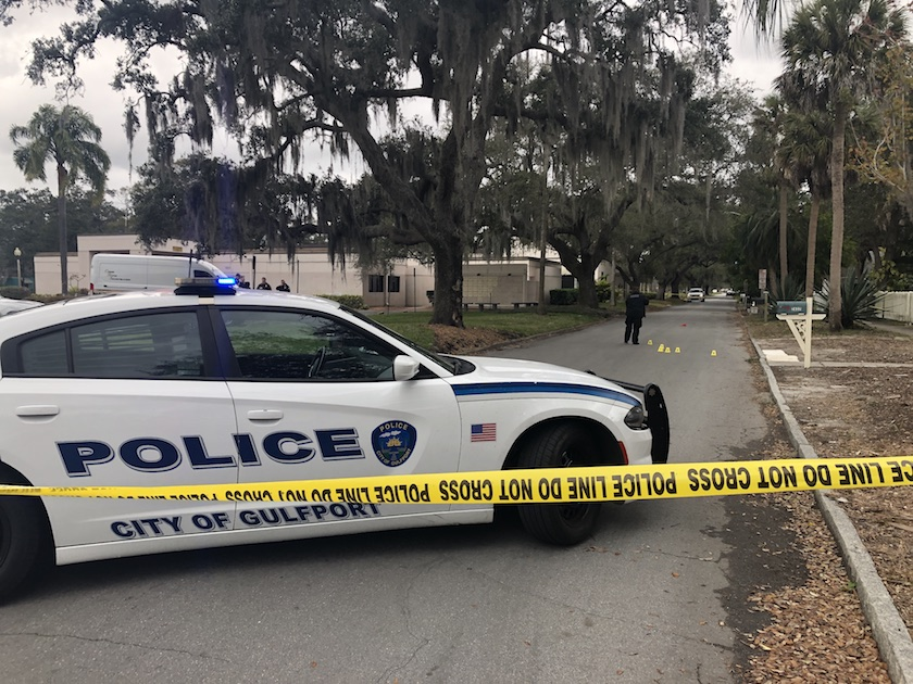 """a police care that says """"Gulfport Florida with a yellow police tape in front and police in background."""